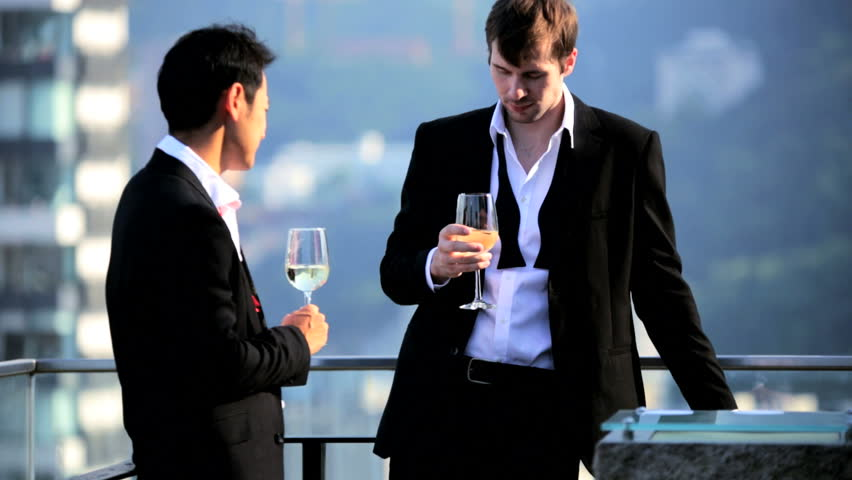 Successful young male Asian Chinese Caucasian business associates dressed evening clothes enjoying evening drinks luxury rooftop bar city downtown