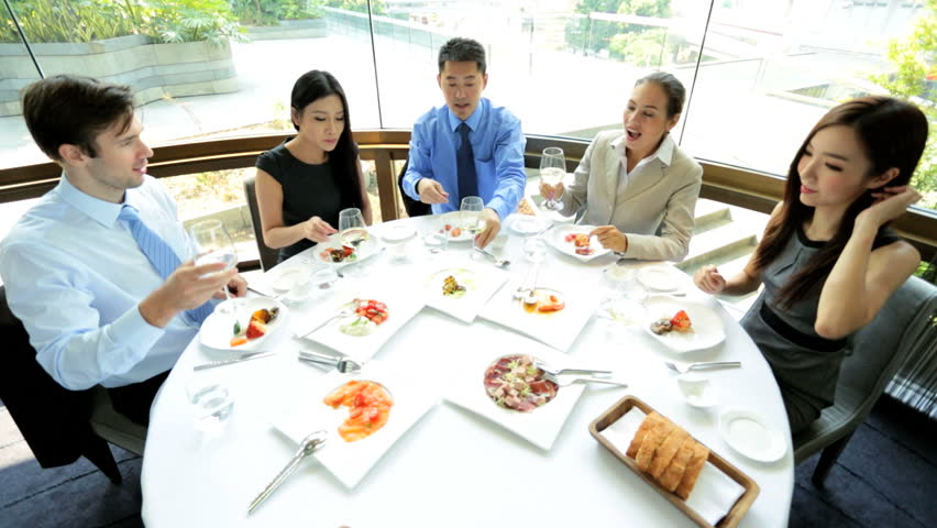 Successful male female Asian Chinese Caucasian advertising executives toasting each other news success dining restaurant | Shutterstock HD Video #6677699