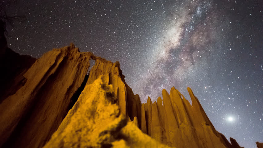 Linear, pan and tilt timelapse of an abstract landscape with eroded sand formations and bizarre structures at night while the Milky Way moves across.
