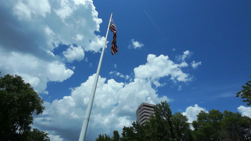 An American flag flying high in a cloud dappled summer sky, with an office building near and trees. - HD stock video clip