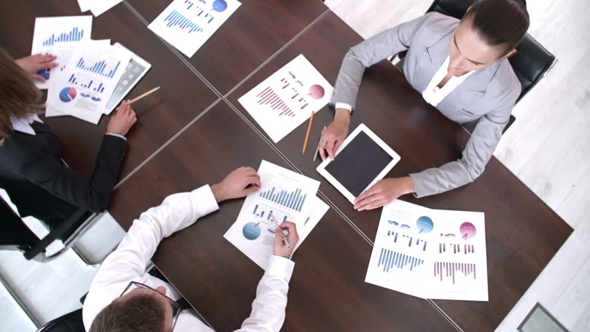 High angle panning shot of people at business meeting with graphic documents | Shutterstock HD Video #6696365