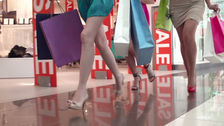 Low angle of unrecognizable girls running with shopping bags on high heels in slow motion