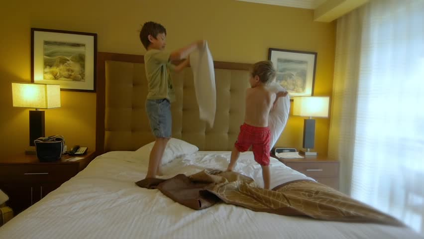 Two boys having a pillow fight on a king size bed. slow motion video clip - HD stock video clip