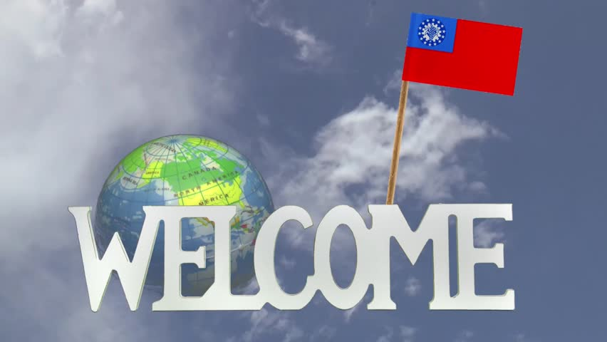 The word WELCOME in front of a turning globe and moving clouds in a blue sky with tooth pick and a small paper flag of MYANMAR - HD stock footage clip