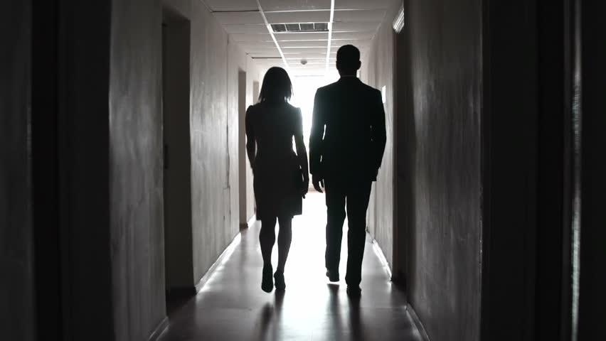 Camera following two unrecognizable people strolling along dark hotel floor