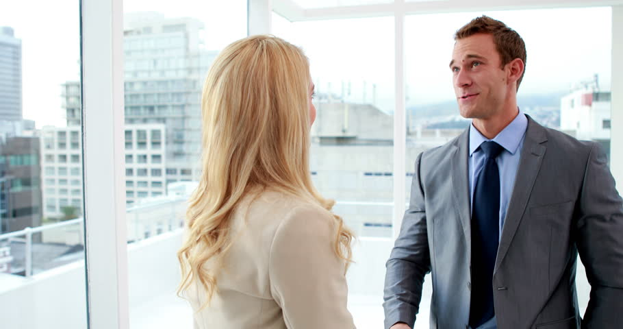 Handsome businessman shaking hands with blonde colleague in the office - 4K stock video clip