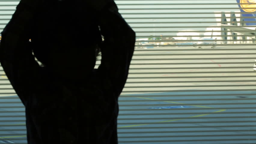 Silhouette of small boy standing on the airport   - HD stock footage clip