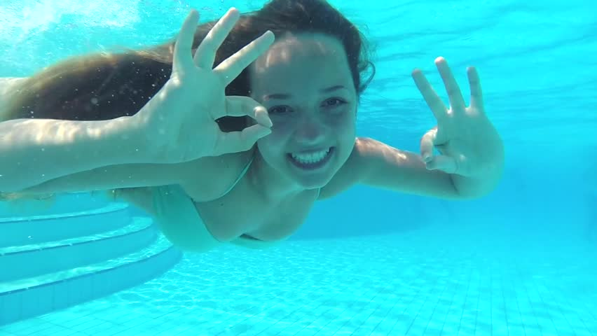 Beauty young woman swimming underwater in swimming pool. Underwater view happy diving teen girl with long hair smiling and waving at camera. Slow motion video footage HD 1080p - HD stock video clip