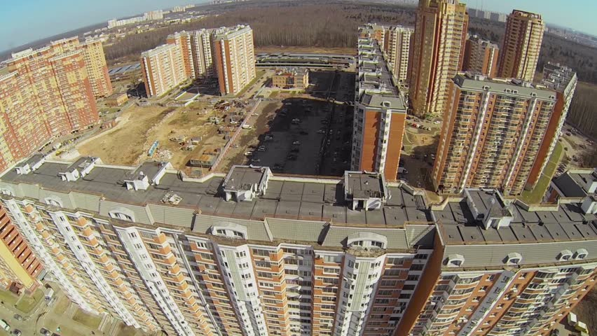 Cars ride near tall dwelling house at city outskirts in sunny day. Aerial view - HD stock footage clip