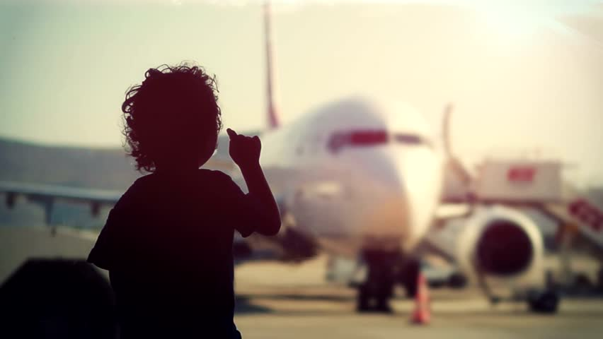 Little boy at the airport terminal. Silhouette of a little boy watching planes at the airport