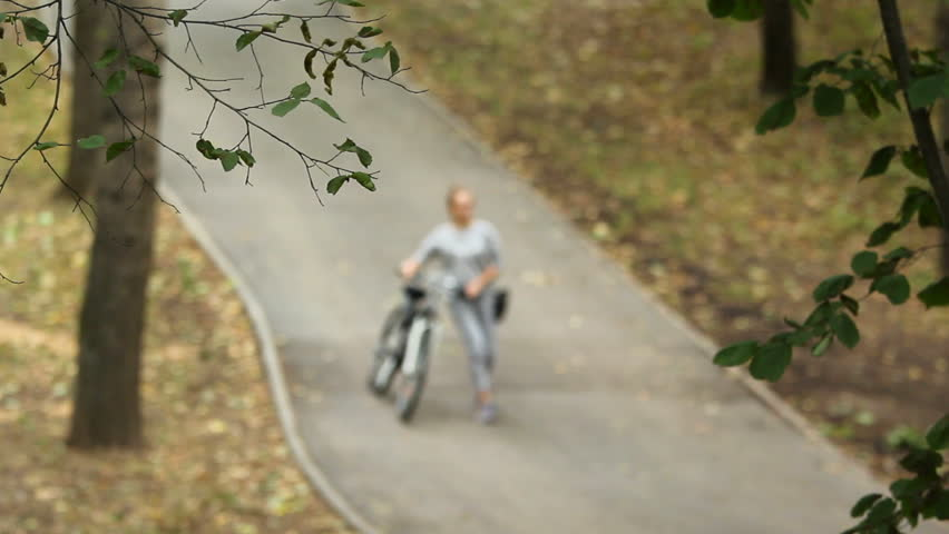 Bike path in the park on a hillside. Downhill walking with a bicycle. Little depth of field