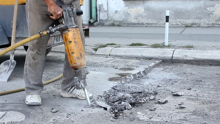 Worker drilling concrete with compressor on the street ...  Worker drilling...