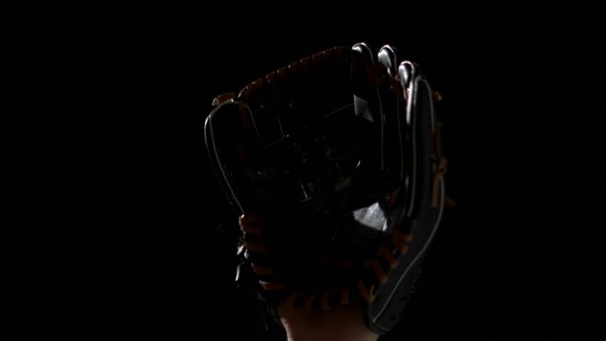 Hand in baseball mitt catching glove in slow motion