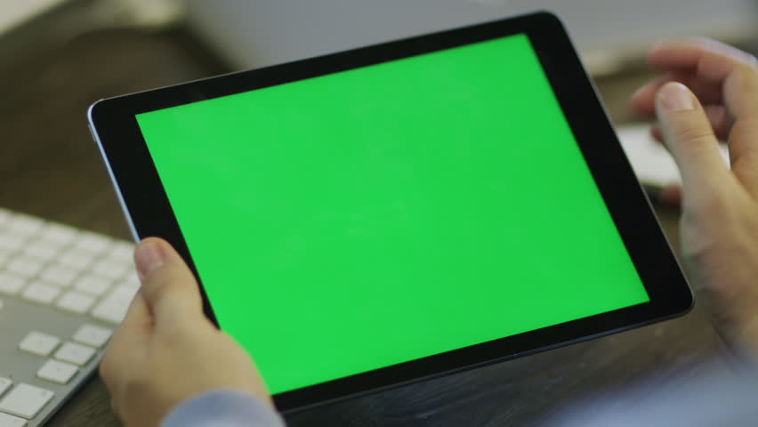 Designer using Digital Tablet with Green Screen at Work in Landscape Mode