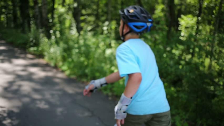 Teenage boy in helmet roller-skates on walkway in summer park