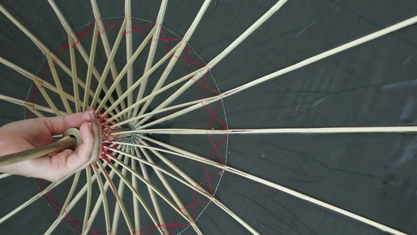 Close up shot of an anonymous woman's hand holding the handle of an old, traditional style, black Asian umbrella with red threads holding together a bamboo frame.