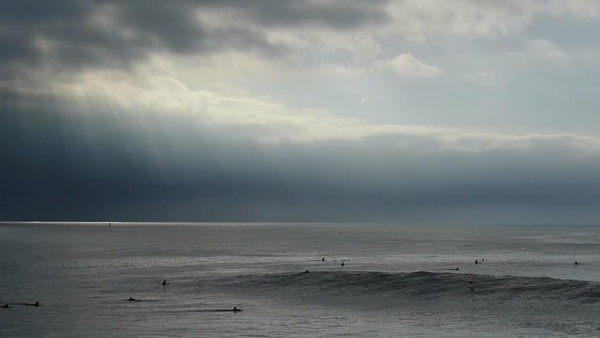 An ocean wave breaks and birds fly by under dark cloud in Santa Cruz, California, USA
