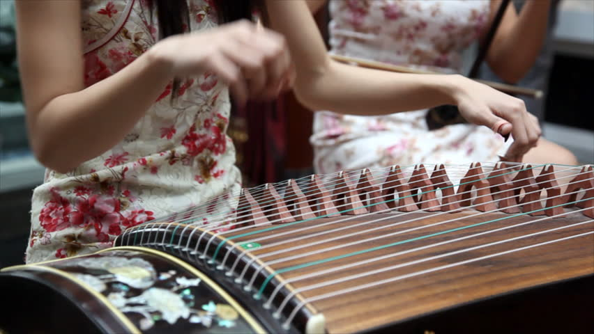 Chinese traditional musician playing chinese guzheng.Guzheng, also called zheng or Chinese plucked zither,is a plucked half-tube zither with movable bridges and  strings.  - HD stock video clip
