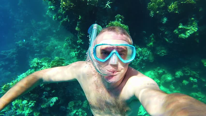 Ocean, summer fun, recreation, holidays, water sports. Man swimming underwater, snorkeling, apnea diving near coral reef, holding GoPro, Go Pro, Go-Pro video camera, Marsa Alam, Red Sea, Egypt. 1of16