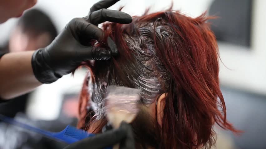 Video showing hairdresser dyeing client's hair.