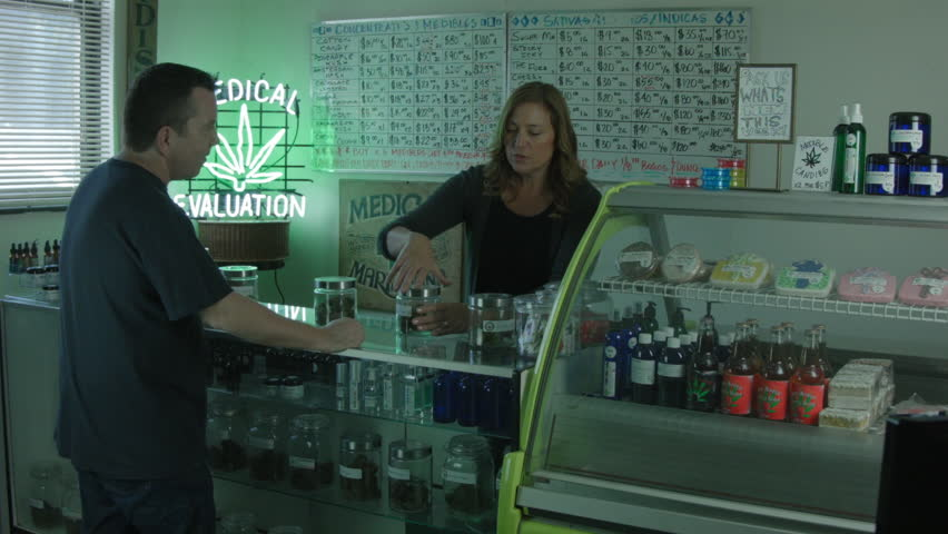 "MEDICAL MARIJUANA DISPENSARY INTERIOR. A FEMALE EMPLOYEE HELPS A MALE CUSTOMER. WIDE SHOT / VERSION 2. ALL LABEL ARTWORK WAS CREATED & CLEARED BY ""PROP HEAVEN"" IN BURBANK, CALIFORNIA."