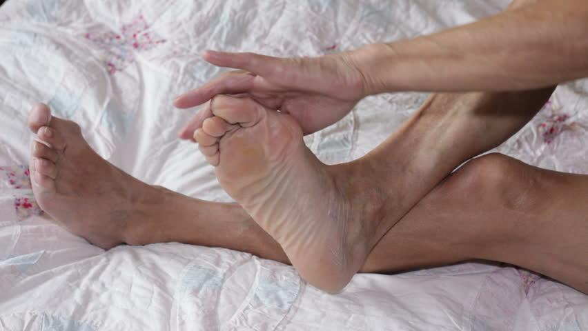 Senior man applying cream on his foot. - HD stock footage clip
