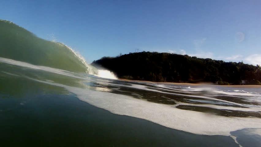 A large ocean wave breaking near the beach in Hawaii.