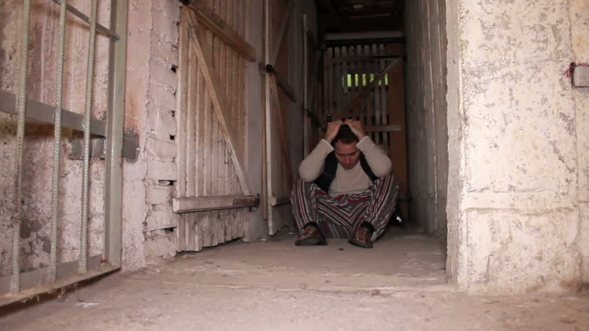Devastated man sitting on the cellar ground when cell door close behind him.