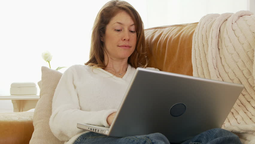 Woman using laptop on couch - HD stock video clip