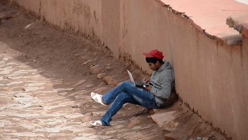 AIT BEN HADDU, MOROCCO, MARCH 9, 2014. A moroccan boy in the age of 17 sitting on an alley playing with his laptop in Ait Ben Haddu, Morocco, on March 9th, 2014.