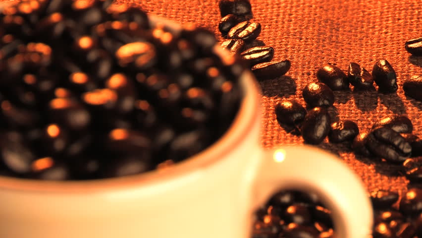 Focus switched from beans in background to cup in foreground. (HD)