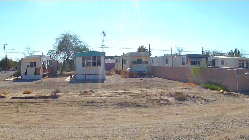 NILAND, CA: December 16, 2014- Shot of driving by mobile homes in a small desert town circa 2014 in Niland. A rural community features neighborhoods filled with trailer park homes.