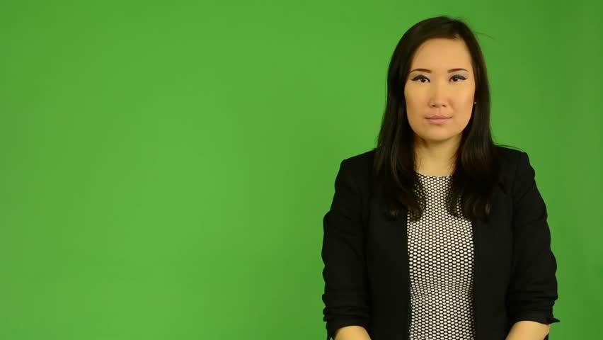 young attractive asian woman talks - green screen studio