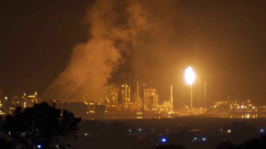 Richmond, California - December, 2014 - Wide shot of flaring from a refinery creating plumes of vapors in the sky.