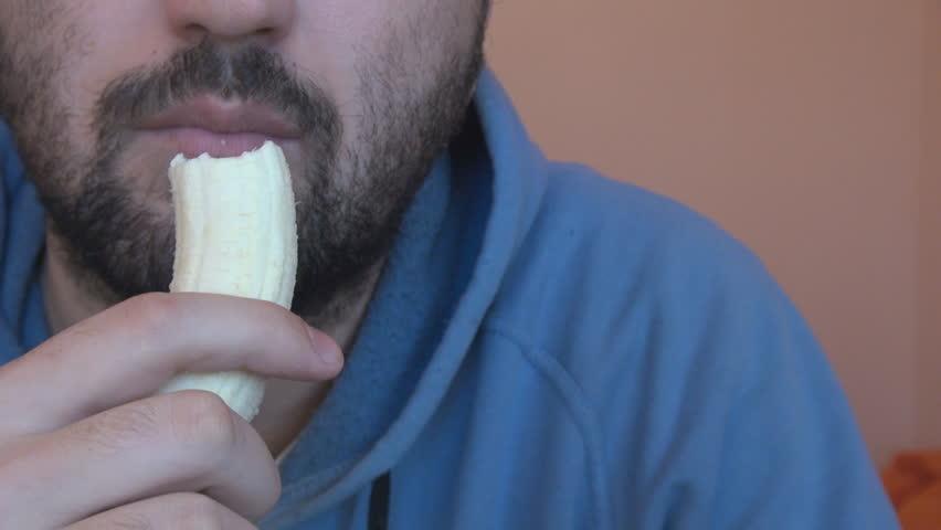 Closeup young man mouth eating ripe banana, healthy diet, black beard person - HD stock video clip