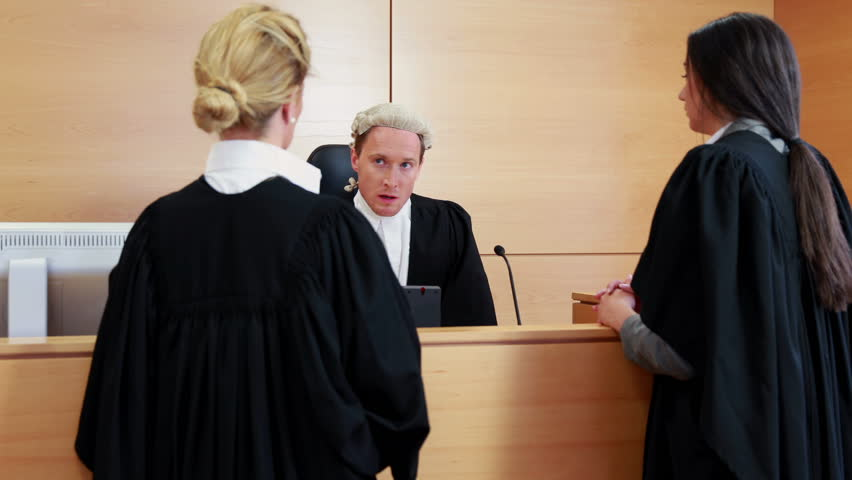 Two lawyers standing and speaking with the judge in court room