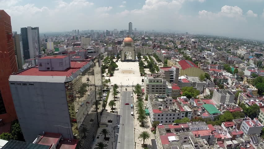 Aerial Shot of Republica's street, esplanade, Revolution Monument and some private and government buildings and a big sidewalk with palms near to Reforma Avenue in Mexico City