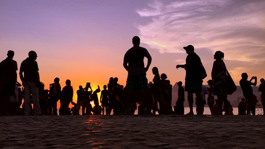 Time lapse of sunset crowd silhouettes at the famous Arpoador Beach Rio de Janeiro Brazil
