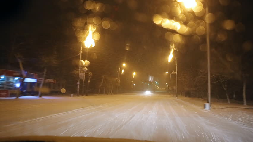 Snow-covered winter road from the windshield of the car at night in the light of the lamps and automobile headlights. Blizzard and heavy snowfall. - HD stock video clip