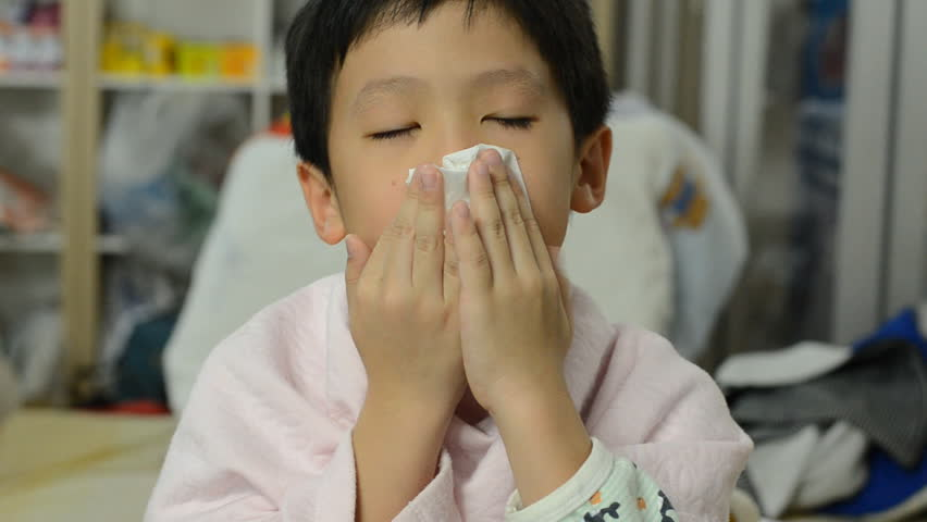 Young Asian boy blows his nose using toilet paper