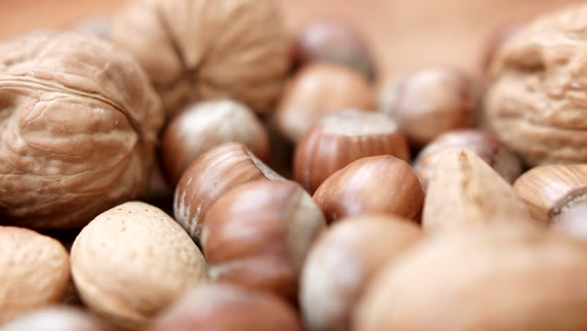 An assortment of nuts HD stock Footage. A close up dolly shot of an assortment of nuts in their shells. ProRes 422.