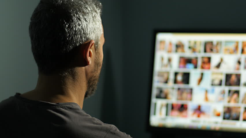 man watches surfing nude sexy girls on the web net looking for virtual sex at night in a dark room,screen is out of focus uhd 4k,useful to represent internet easy porn accessibility and social issue
