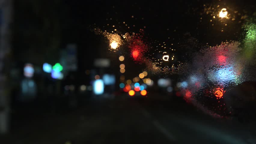 Evening traffic with city lights. Motion blur bokeh pov of a car.Defocussed blurry light from traffic through wet  car window ; Night background; Abstract defocused city street lights - HD stock footage clip