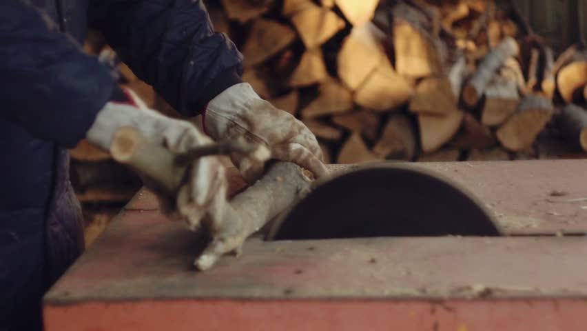 Man chopping firewood with circular saw. Slow motion