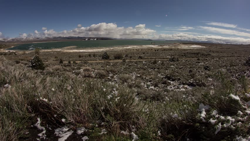TIme lapse of clouds moving above mono lake in a distance.