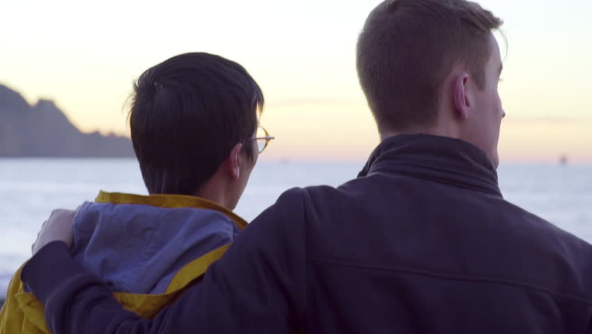 Couple Watch The Sunset At The Beach, Man Puts His Arm Around His Boyfriend's Shoulder And They Walk Closer To The Water