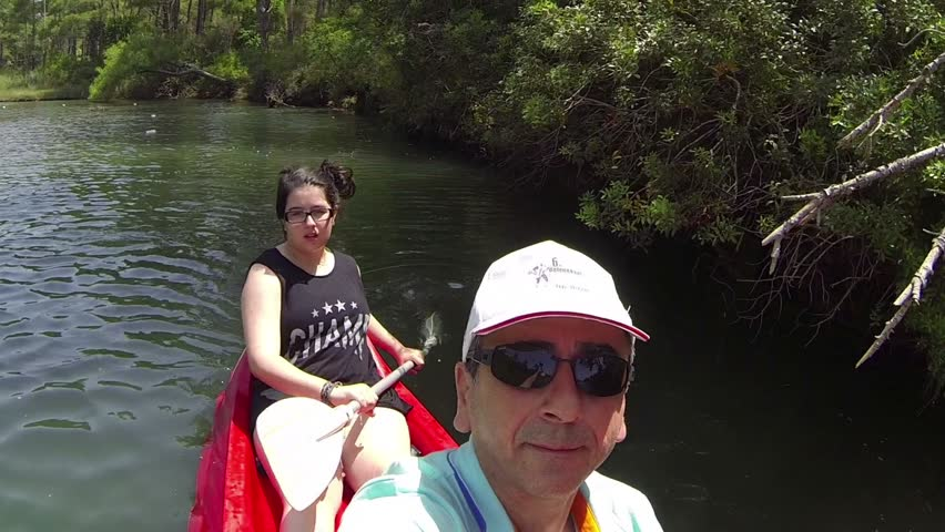 Couple riding canoe in river. Father and his daughter having fun outdoors. Paddling a small canoe in the river at Kamp Amazon in Marmaris, Turkey