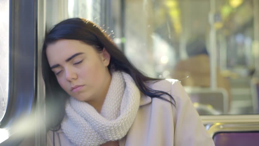 Mixed Race Young Woman Sleeps On The Train As It Moves Through City (Lens Flare)