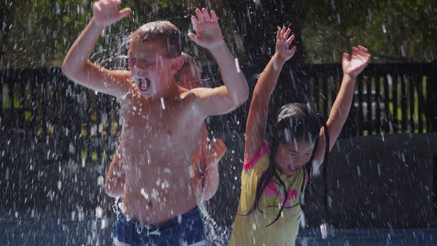 Children playing in water fountains on summer day, slow motion