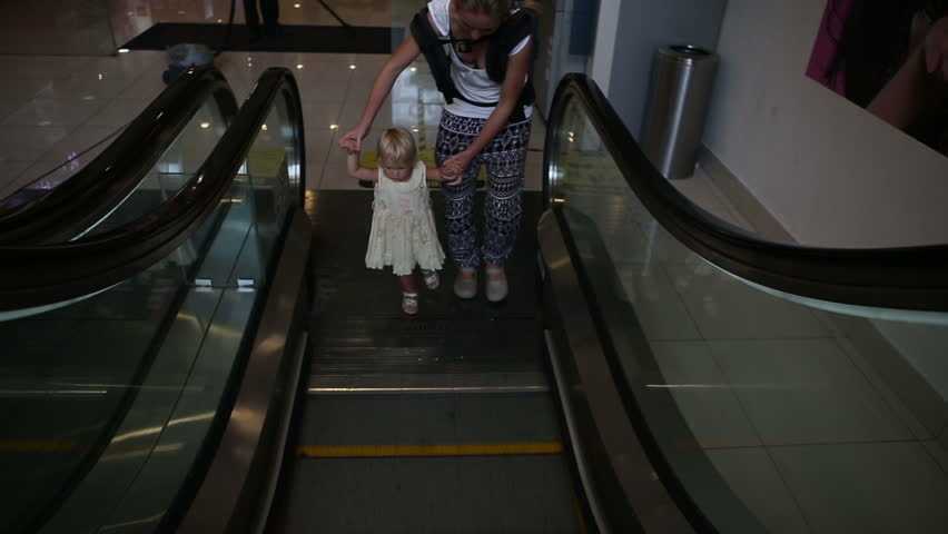 Small blonde child and her mother move on escalator for first time in trade center   Shutterstock HD Video #9094127